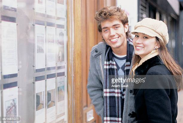 Portrait of Student Couple Next to an Estate Agent's Window