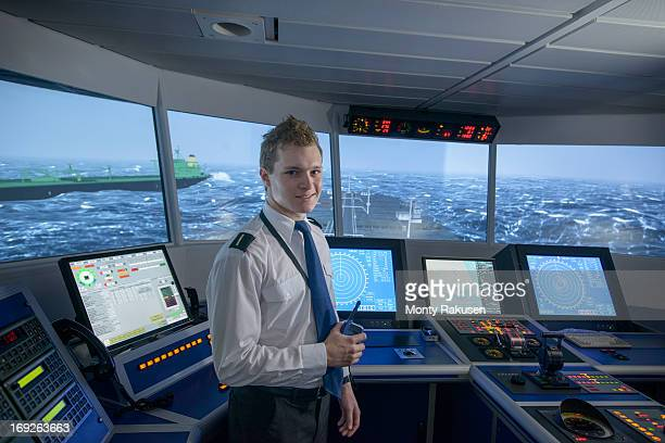 Portrait of student holding communication radio in ship's bridge simulation room