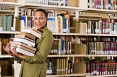 Portrait of student holding pile of books at library