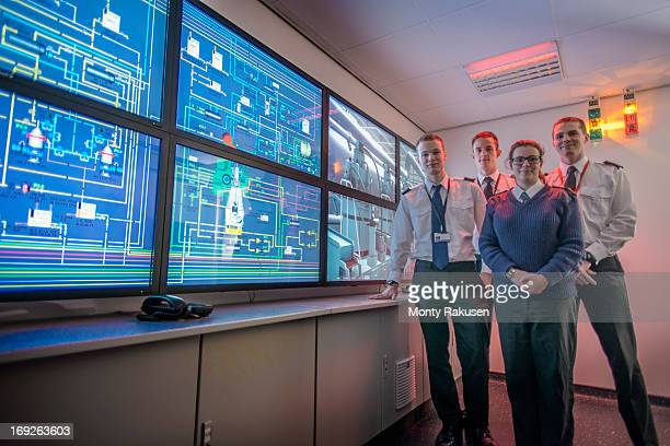 Portrait of students in front of monitors in ship's engine room simulator