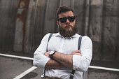 portrait of stylish bearded man in sunglasses sitting on parking place