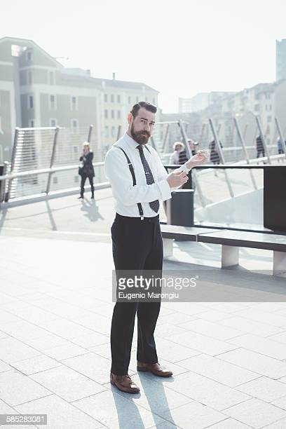 Portrait of stylish businessman fastening shirt cuffs on footbridge