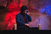 Portrait of stylish Deejay playing at Dj mixer on light studio background.