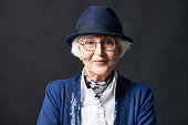 Close-up portrait of stylish old lady in round glasses and hat standing on dark wall background, looking at camera confidently and smiling slightly