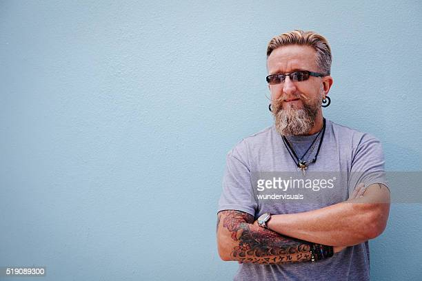 Portrait of stylish mature man with beard and tattoo