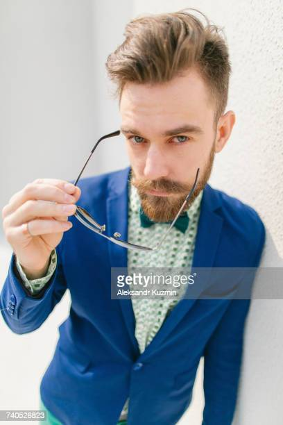 Portrait of stylish Middle Eastern man with beard holding eyeglasses
