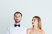 Close up colour studio portrait of stylish young couple, pretty woman with naked shoulders and handsome man, wearing white shirt and the bow tie, against plain studio background.