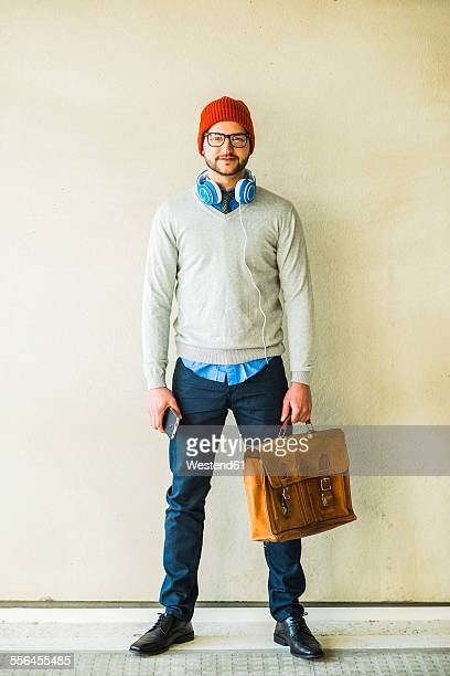 Portrait of stylish young man with leather bag