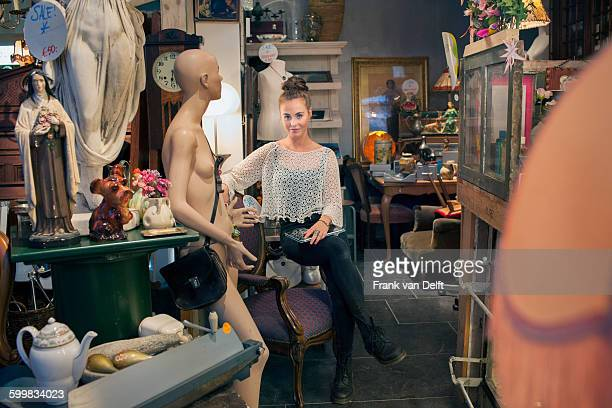 Portrait of stylish young woman sitting in vintage shop