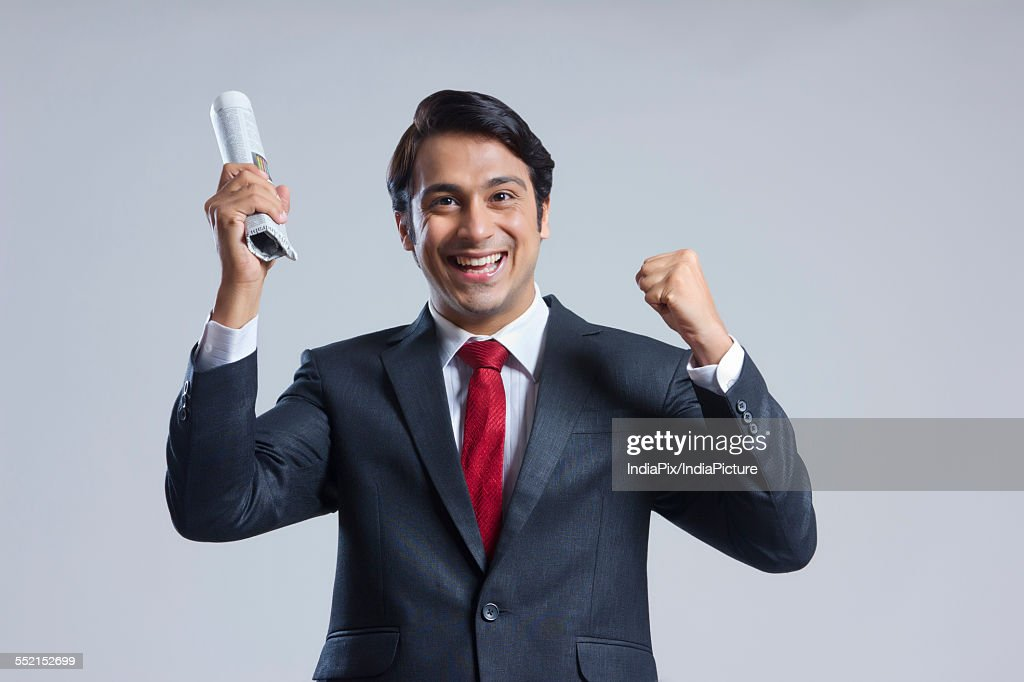 Portrait of successful businessman holding newspaper against gray background : Stock Photo