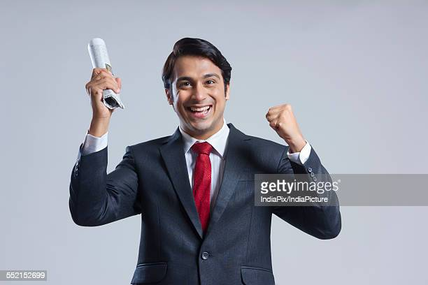 Portrait of successful businessman holding newspaper against gray background