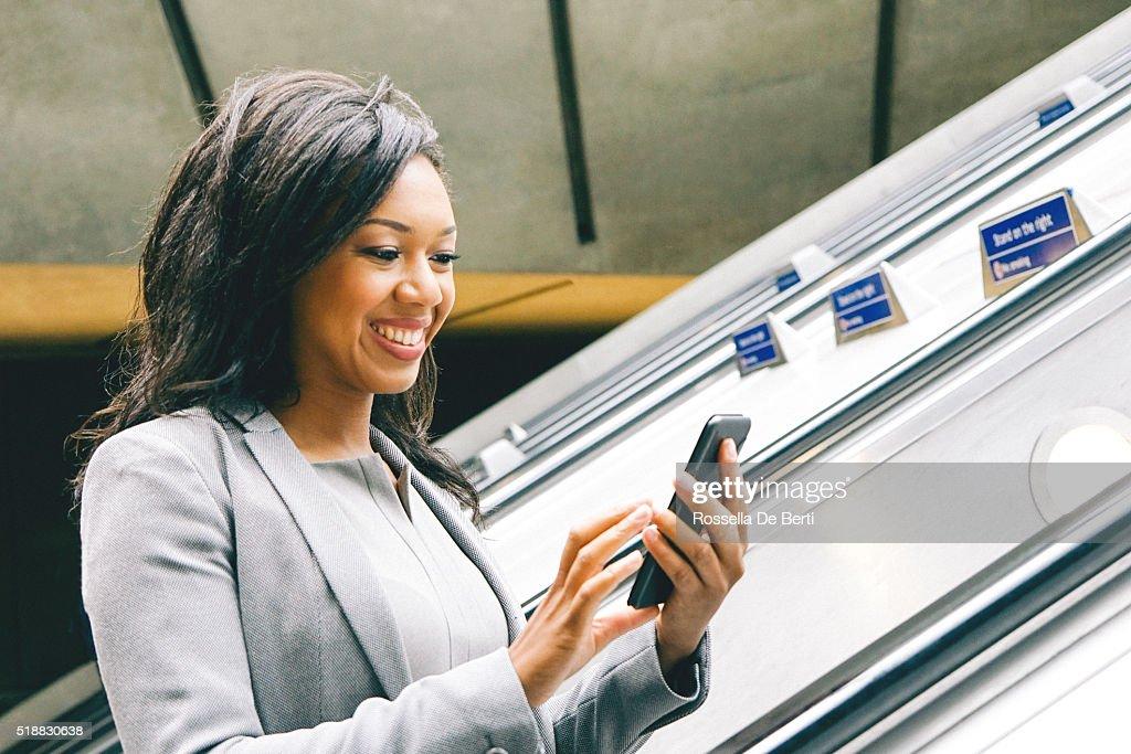 Porträt des erfolgreichen Geschäftsfrau mit Smartphone auf U-Bahn Rolltreppen : Stock-Foto
