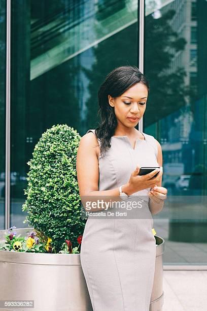 成功のビジネスウーマンの肖像画のスマートフォンを使用して屋外