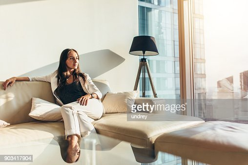 Portrait of successful businesswoman wearing elegant formal suit sitting on leather sofa relaxing after work at home : Foto de stock