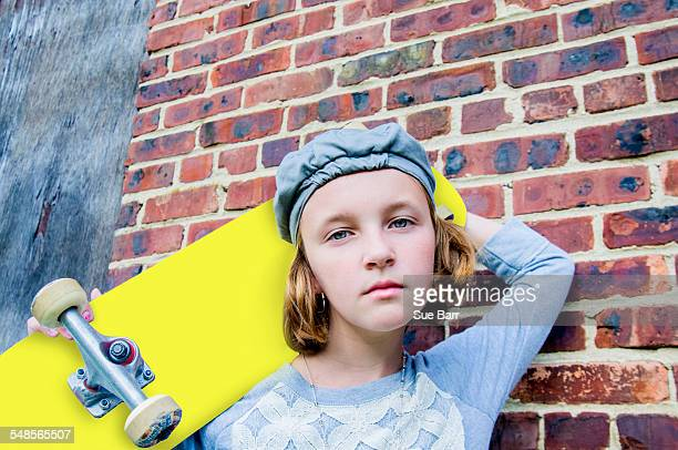 Portrait of sullen tomboy skateboarder girl leaning against brick wall