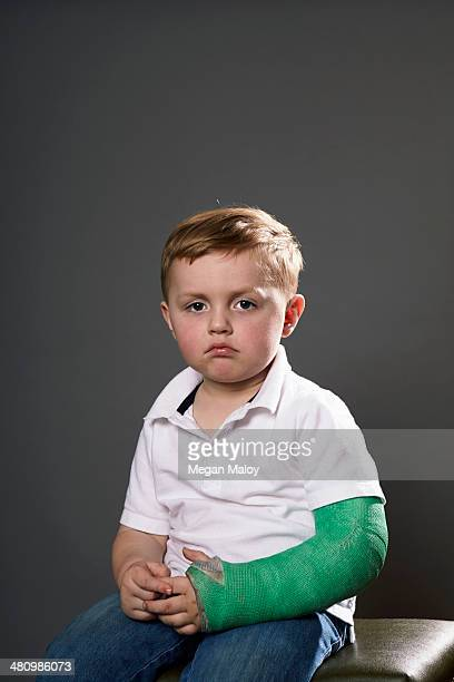 Portrait of sullen young boy with plaster cast on arm