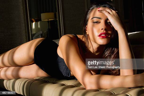 Portrait of sultry young woman reclining on bedroom seat