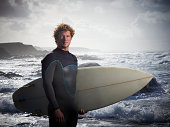 Portrait of surfer with board on coastline.