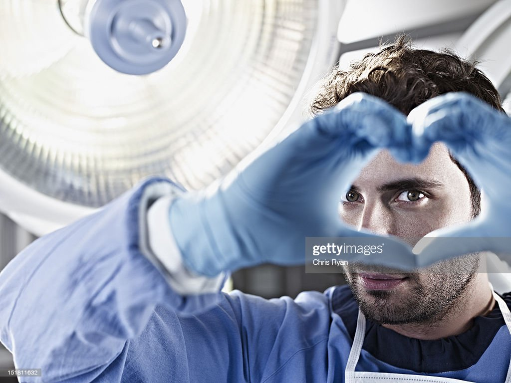 Portrait of surgeon making heart-shape with hands under surgical light : Stock Photo