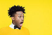 Portrait of shocked nerdy young afro american man wearing yellow sweater and black bow tie looking at copy space with mouth open against yellow background.