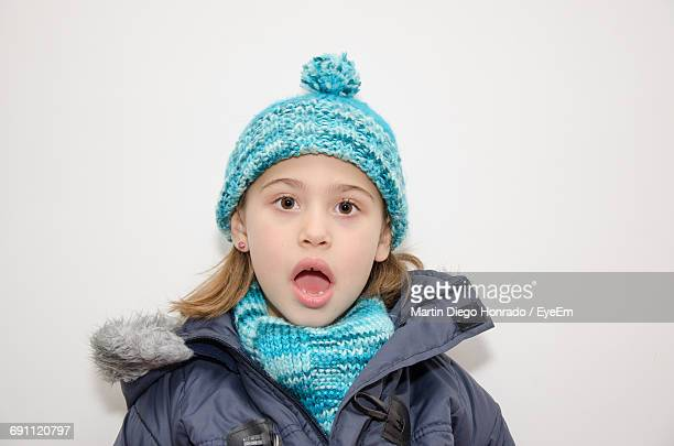 Portrait Of Surprised Girl In Warm Clothes Against White Background