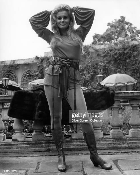 Portrait of SwedishAmerican actress AnnMargret as she poses with her arms over her head dressed in a blouse fringed belt shorts and boots a fur coat...