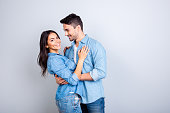 Portrait of sweet hispanic cute lovers, bearded man hugging woman and looking at her, pretty woman looking at camera over grey background