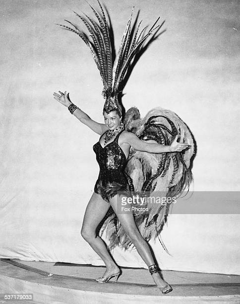Portrait of swimmer and actress Esther Williams wearing a feather showgirl costume for the 'Aqua Spectacle of 1956' show Empire Pool Wembley London...