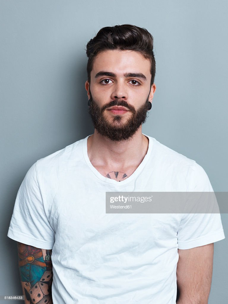 Portrait of tattooed brunette man in front of gray background