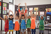 Portrait of teacher and schoolkids having fun in drawing class