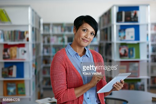 Portrait of teacher holding tablet at library : Stock Photo