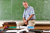 Portrait of teacher sitting on desk in front of chalkboard