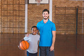 Portrait of sports teacher standing with his student in basketball court at school gym