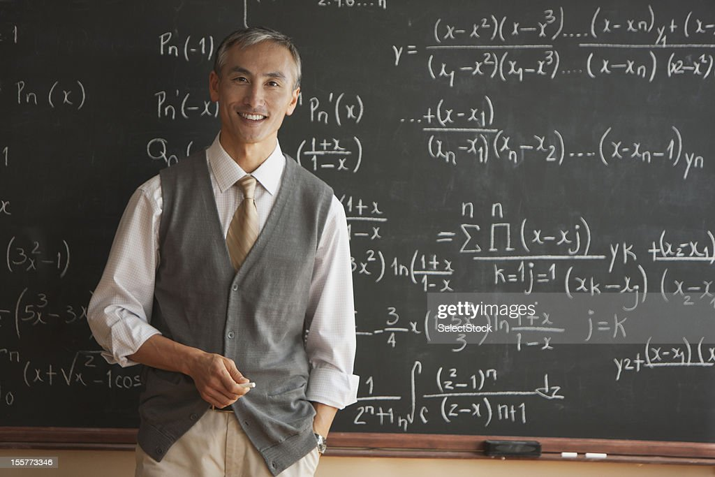 Portrait of teacher with in front of blackboard : Stock Photo