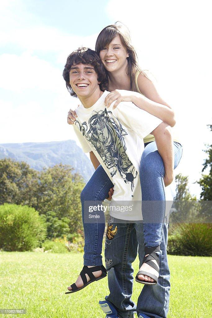 Portrait of teen boy giving girl a piggyback : Stock Photo