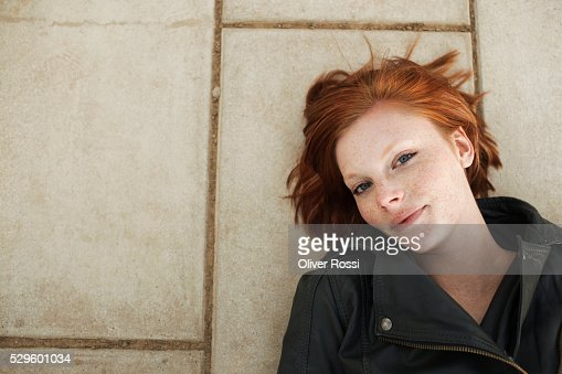 Portrait of teen (16-17) girl lying on pavement : Foto de stock