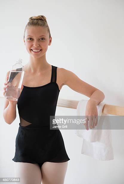 Portrait of teenage (16-17) ballet dancer standing at barre and holding water bottle