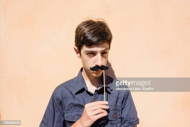 Portrait Of Teenage Boy Holding Stick With Mustache Against Wall