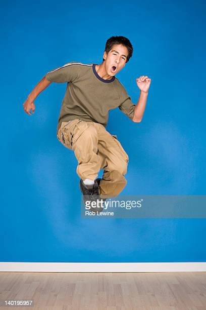 Portrait of teenage boy (16-17) jumping
