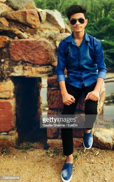 Portrait Of Teenage Boy Posing While Sitting On Rock