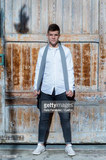 Portrait Of Teenage Boy Standing Against Weathered Wooden Wall