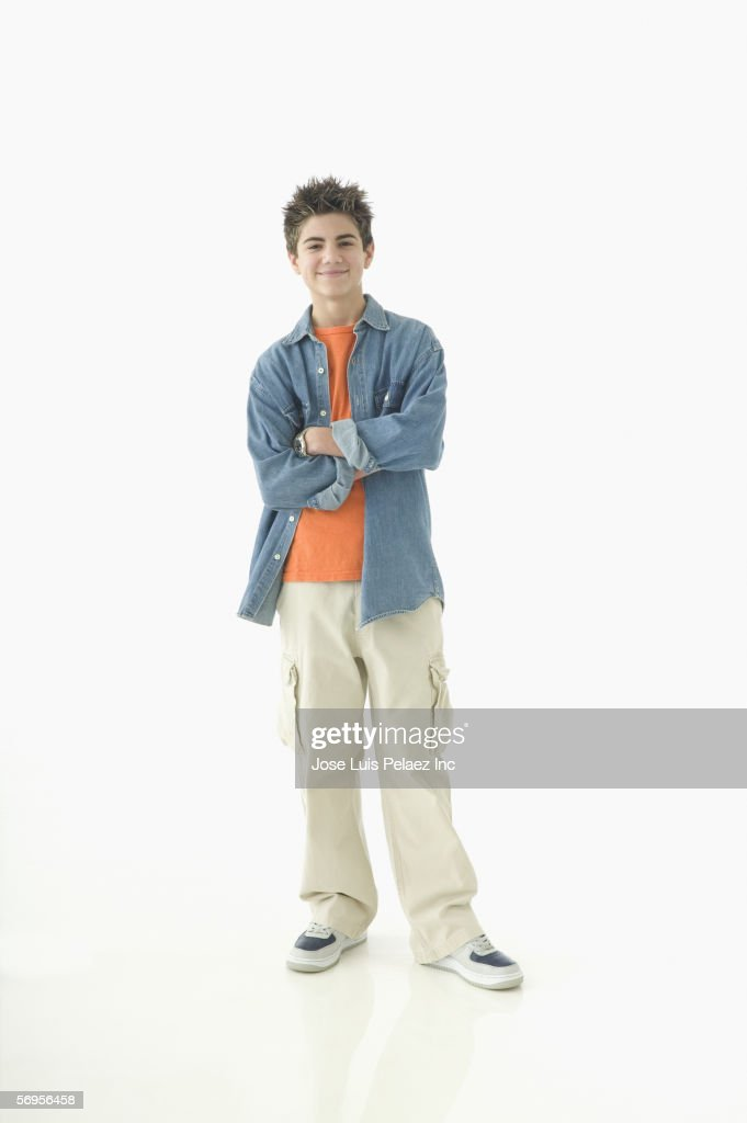 portrait of teenage boy standing with arms crossed stock