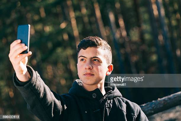Portrait of teenage boy taking a selfie with his mobile phone