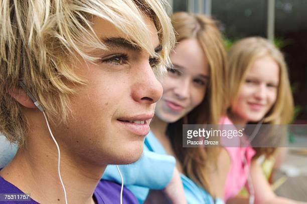 Portrait of teenage boy with earphones, 2 teenage girls in background