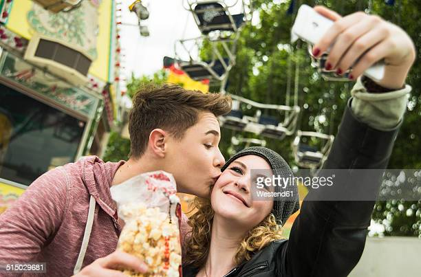 Portrait of teenage couple with popcorn photographing themself at fun fair