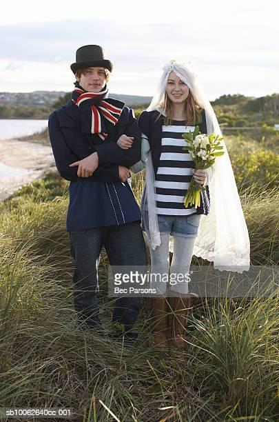 Portrait of teenage girl (16-17) and teenage boy (14-15) at seashore, mock wedding