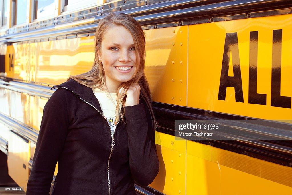 Portrait of teenage girl at U.S. yellow school bus : Stock Photo