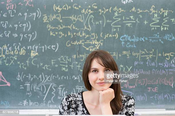 Portrait of teenage girl (16-17 years) by blackboard