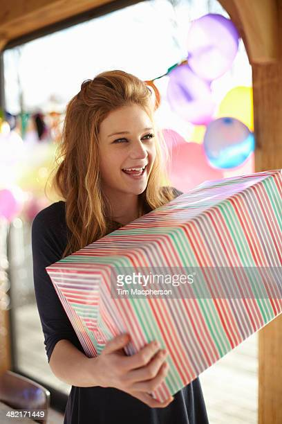 Portrait of  teenage girl holding large birthday gift