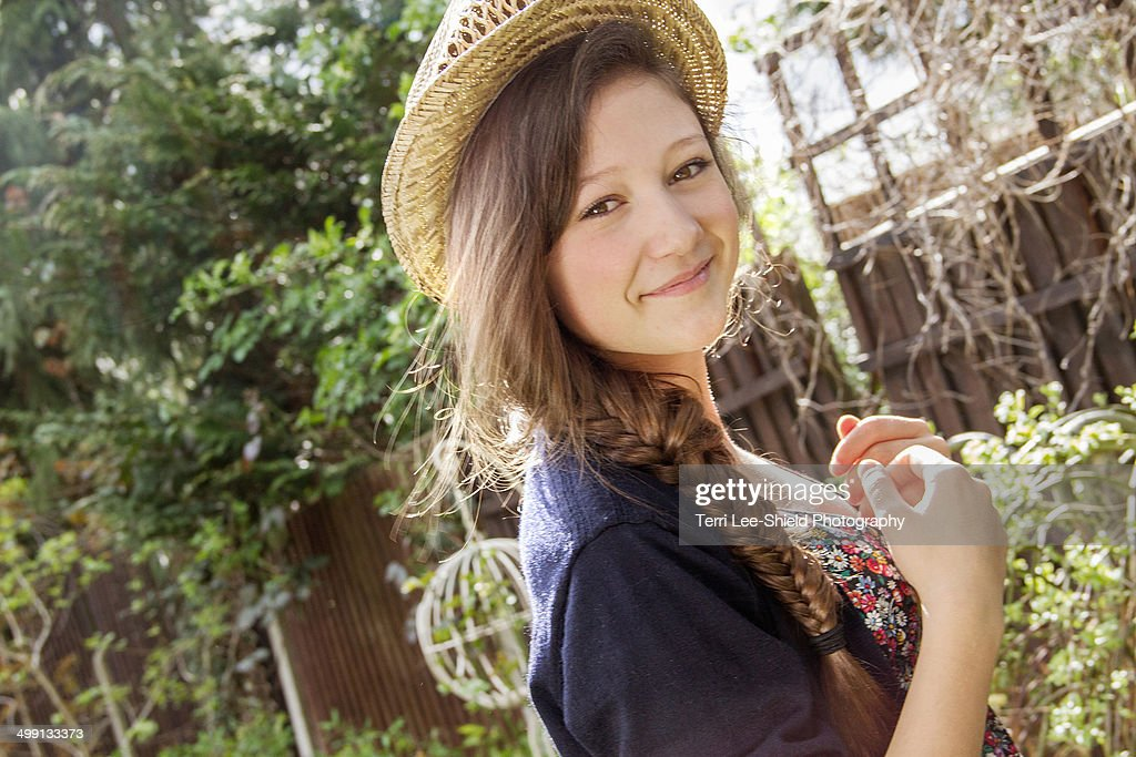 Portrait of teenage girl in straw hat in garden
